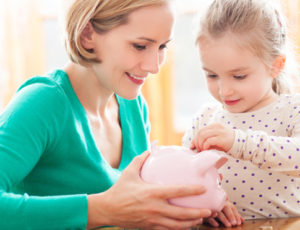 Woman teaching little girl how to use a piggy bank