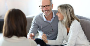Smiling couple speaking with an advisor