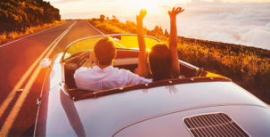 Couple driving in a convertible during sunset