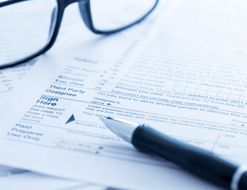 Tax forms with pen and glasses